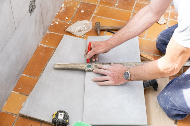 O ladrilhador mede o ladrilho antes de cortá-lo