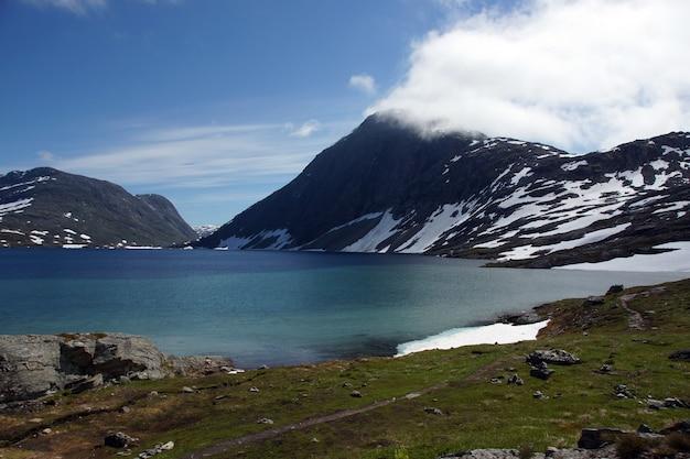 O lago azul fica no sopé das montanhas cobertas de neve no verão na noruega