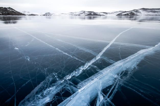 O lago baikal está coberto de gelo e neve, frio e geada fortes, gelo azul claro e espesso