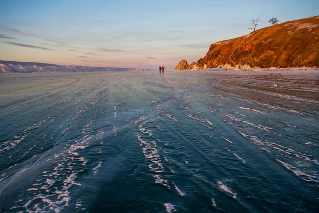 O lago baikal está coberto de gelo e neve, um frio forte e um gelo azul claro e espesso. sincelos pendurados em rochas