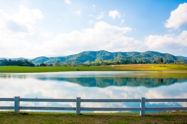 O lago e a montanha com cerca viva branca sobre fundo de céu azul