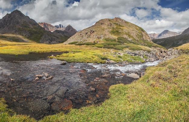 O lago entre a tundra da montanha e prados verdes