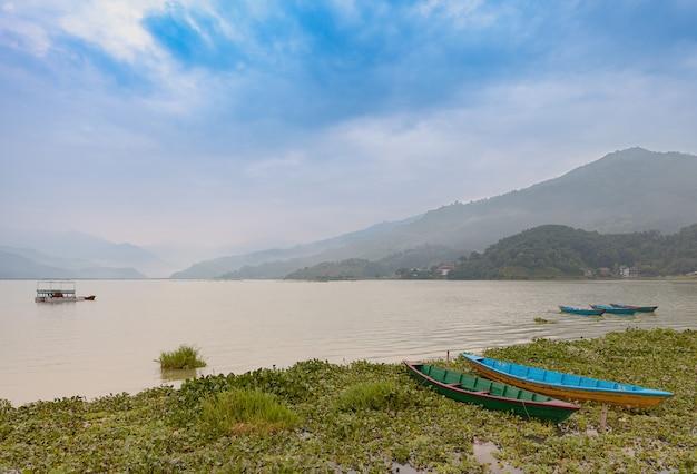 O lago fewa com cena nebulosa, pokhara, nepal