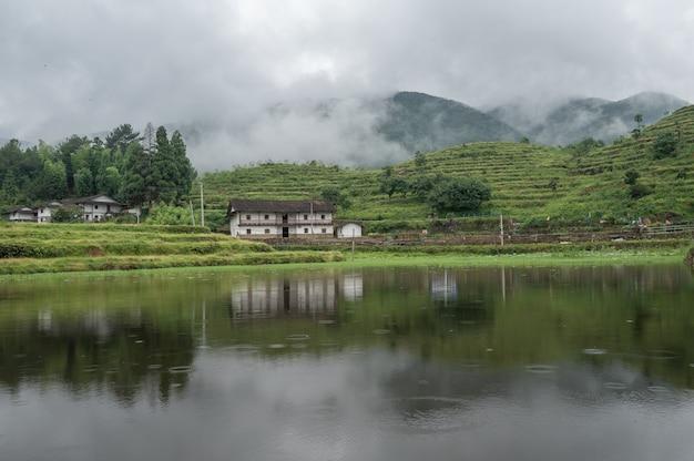 O lago refletia a montanha com casas e névoa na montanha
