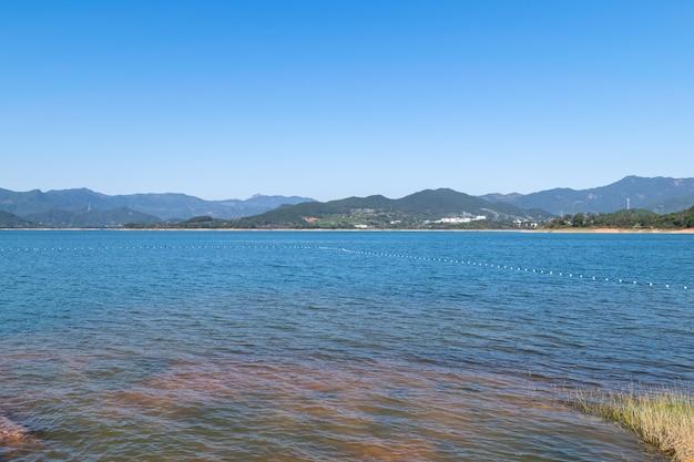O lago sob o céu azul tem água azul e terra vermelha Foto Premium