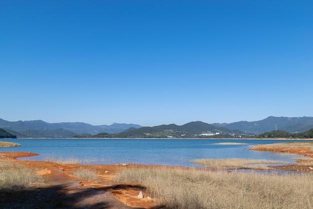O lago sob o céu azul tem água azul e terra vermelha