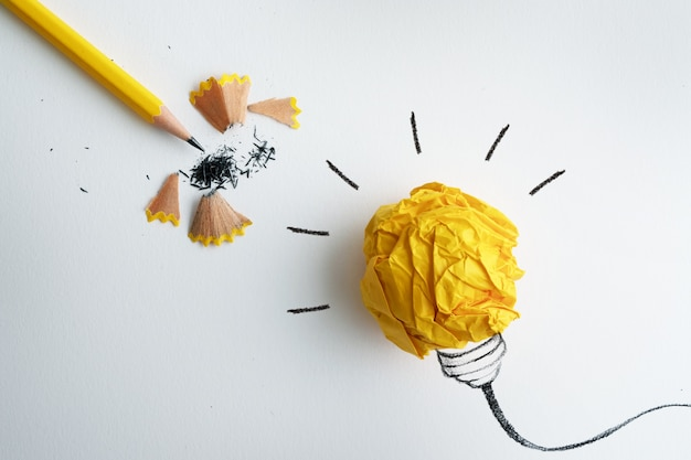 O lápis amarelo com bola de papel amarelo amassado e mão desenhada uma lâmpada