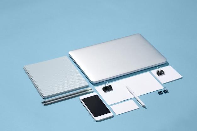 O laptop, canetas, telefone, nota com tela em branco na mesa