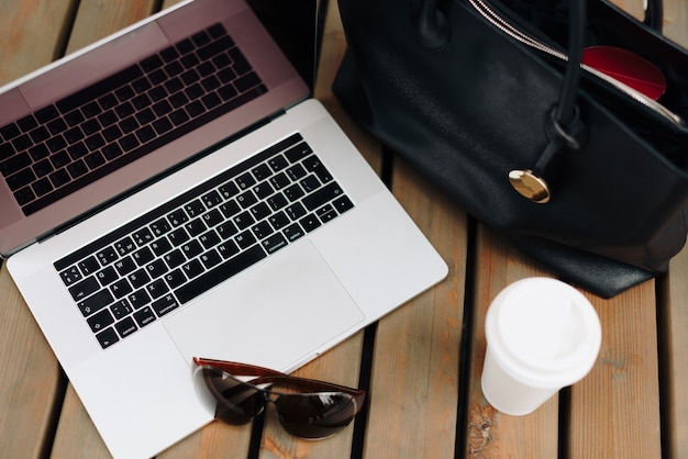 O laptop com a bolsa da mulher e café ao ar livre