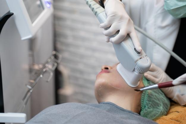 O laser ou a freqüência que endurece a pele que enfrenta o procedimento do tratamento do elevador envolvem. jovem mulher que recebe o tratamento do laser