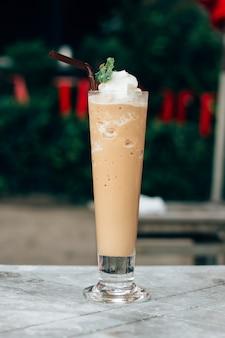 O latte misturou com o creme chicoteado, trajeto de grampeamento. liquidificador de café gelado em um copo.