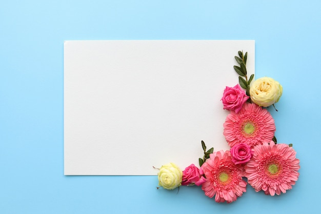O layout das flores da primavera em uma superfície azul