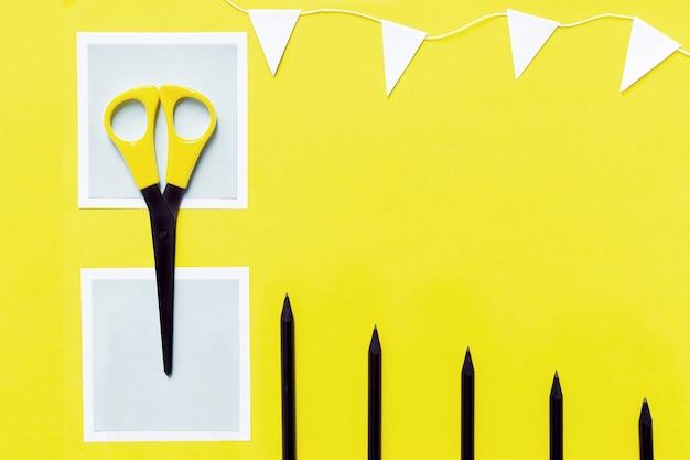O layout de papel branco, lápis pretos, tesoura e guirlanda branca em amarelo.