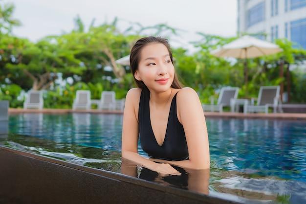 O lazer asiático novo bonito da mulher do retrato relaxa o sorriso em torno da piscina exterior para férias