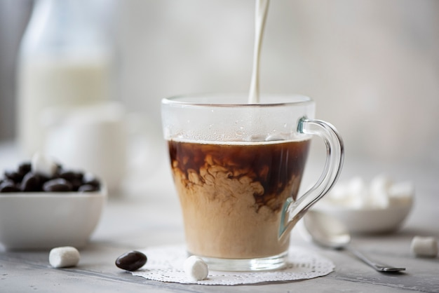 O leite é derramado em uma xícara de café preto quente