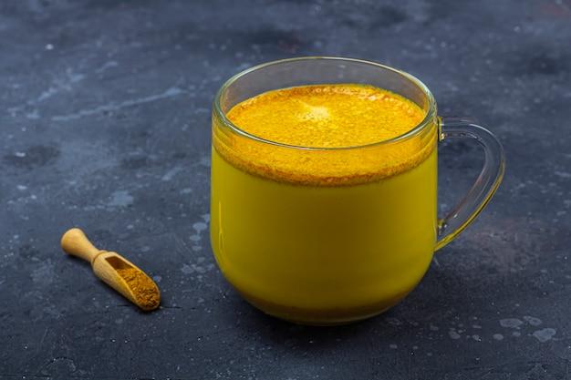 O leite tradicional açafrão da bebida indiana é o leite dourado na caneca de vidro com canela, estrela de anis, açafrão em fundo escuro. perda de peso, bebida saudável e orgânica