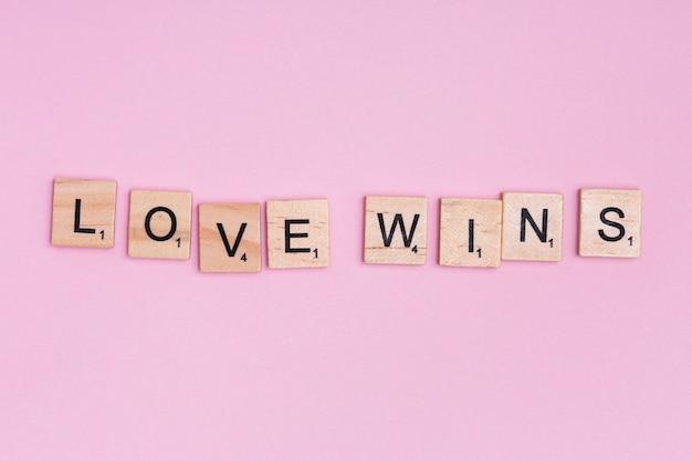 O lema lgbt love wins em fundo rosa