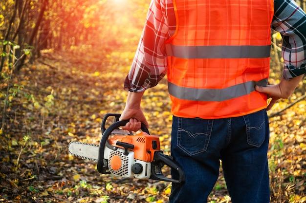 O lenhador está usando equipamento de proteção e segurando uma serra elétrica na mão
