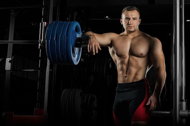 O levantador de peso apoia a mão na barra e olha ameaçadoramente para a frente.