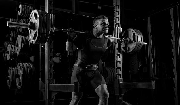 O levantador de peso está se preparando para levantar uma barra muito pesada. ele exala sem fôlego e se esforça tanto quanto possível antes de realizar o exercício.