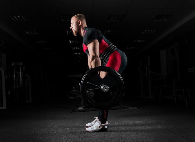 O levantador de peso realiza um exercício chamado levantamento terra. ele fixou o peso