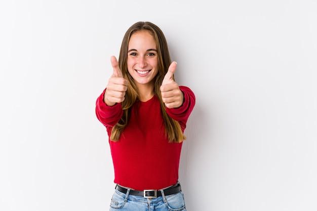 O levantamento caucasiano novo da mulher isolado com polegares levanta, felicidades sobre algo, apoia e respeita o conceito.