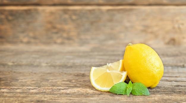 O limão inteiro e suas rodelas com folha de hortelã na mesa de madeira
