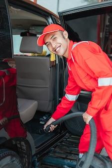 O limpador de carro asiático usa uniforme sorridente vermelho enquanto limpa o chão do carro com aspirador de pó no salão do carro