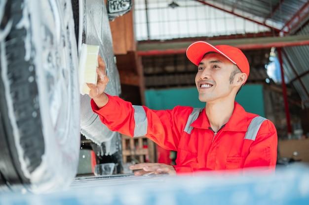 O limpador de carros masculino usa uniforme vermelho e chapéu sorridente enquanto lava o carro com uma esponja espumosa no salão de beleza