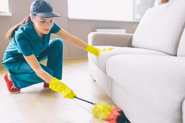 O limpador está sentado na posição de esquadrão e segurando a escova contra poeira. ela está limpando embaixo do sofá. a menina é séria e confusa.
