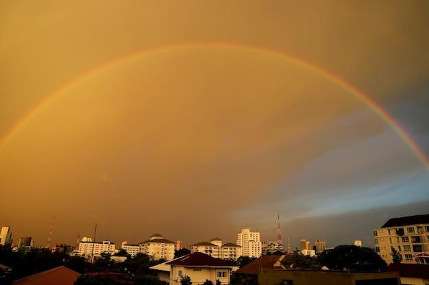 O lindo arco-íris depois da chuva na cidade à noite natureza e conceito de construção
