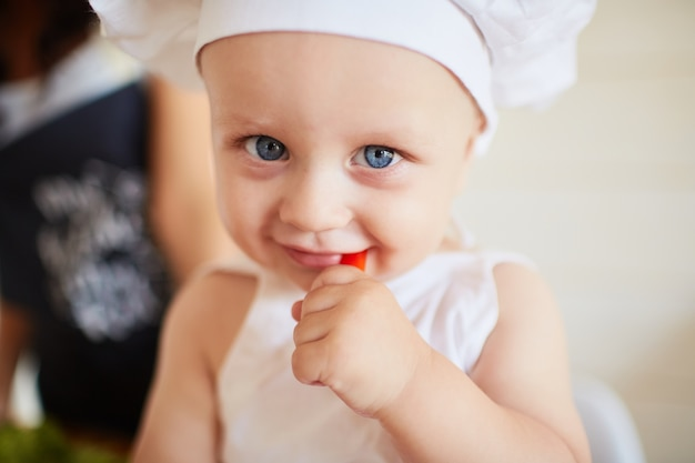 O lindo bebê comendo um papel vermelho