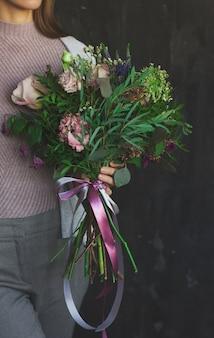 O lindo buquê de flores em estilo rústico nas mãos das mulheres