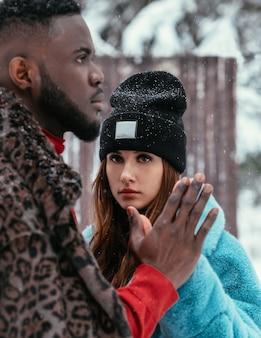 O lindo casal afro-americano e uma garota de aparência europeia em uma floresta de inverno no contexto do verão em roupas elegantes. o conceito de verão no inverno.