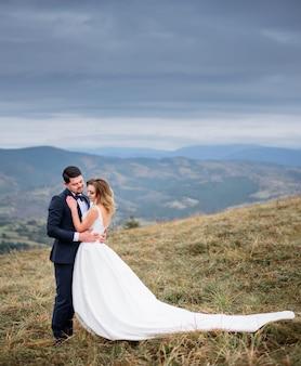 O lindo casal apaixonado abraçando e permanente no campo