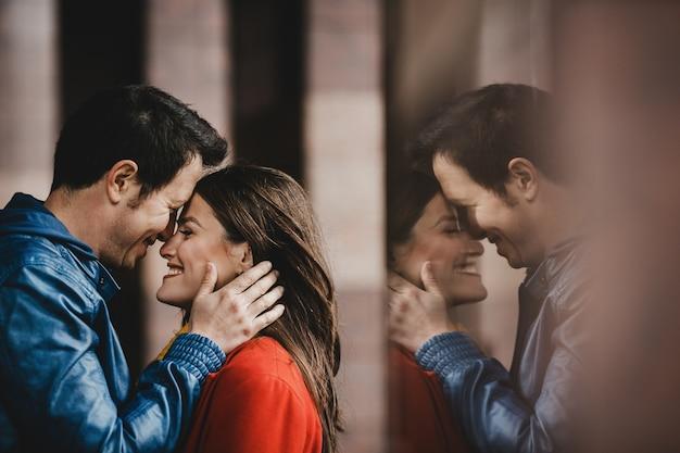 O lindo casal apaixonado, abraçando-se perto da parede