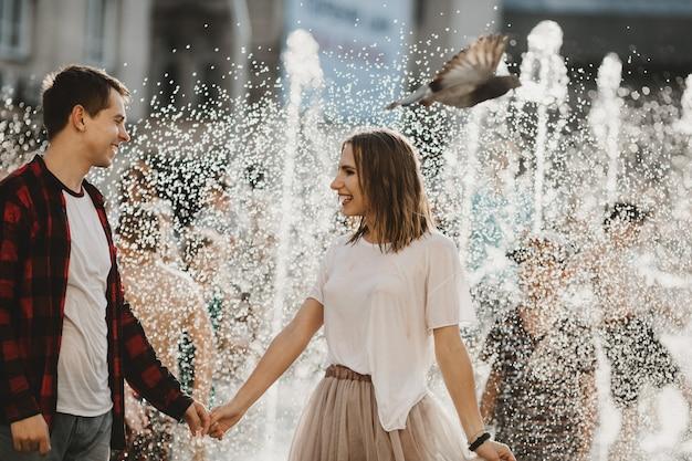 O lindo casal apaixonado andando perto da fonte