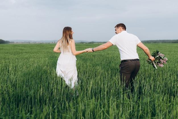 O lindo casal apaixonado caminhando ao longo do campo