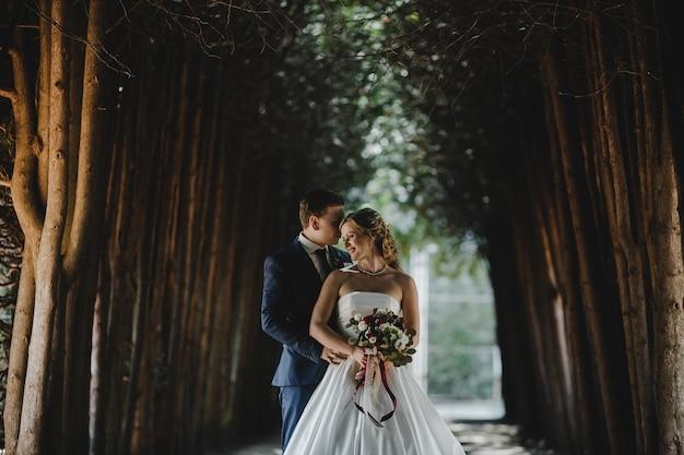 O lindo casal apaixonado em pé na floresta