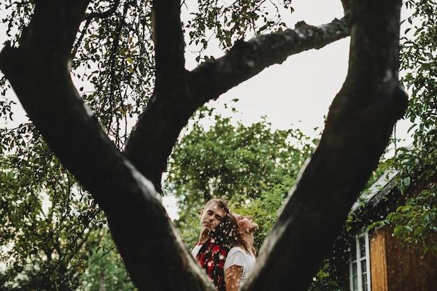 O lindo casal apaixonado se abraçando no parque sob chuva
