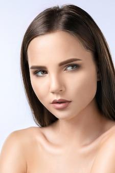 O lindo rosto de uma jovem com uma pele limpa e fresca