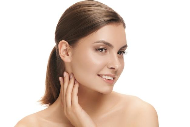 O lindo rosto feminino sorridente feliz. a pele perfeita e limpa do rosto em branco. a beleza, cuidados, pele, tratamento, saúde, spa, conceito cosmético