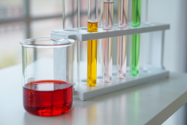O líquido vermelho, amarelo, rosa e verde estão dentro de laboratórios copo