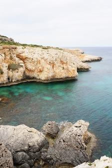 O litoral com montanhas rochosas e águas calmas sob o céu azul