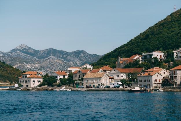 O litoral da cidade de lepetane, em montenegro, perto da travessia de balsa pela baía de kotor
