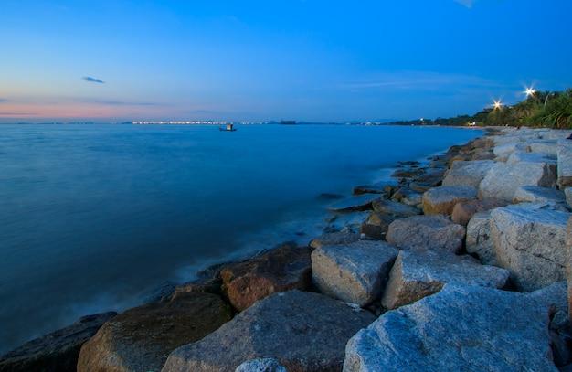 O litoral rochoso com o céu azul e mar azul na tailândia