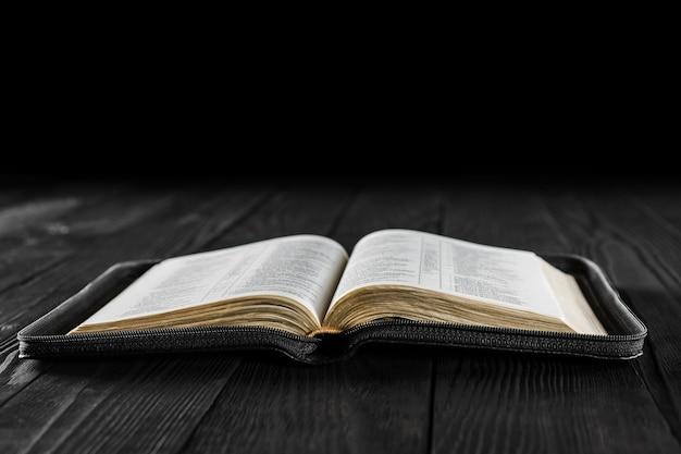 O livro aberto bíblia em madeira preta