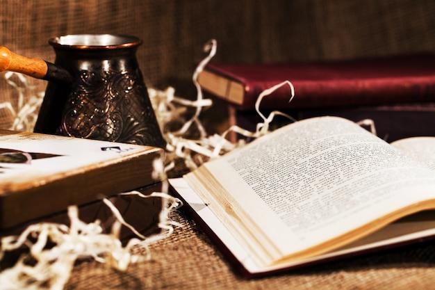 O livro aberto se encontra diante de um cezve com café