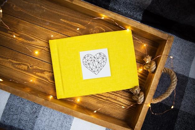 O livro amarelo encontra-se em uma bandeja de madeira com as luzes
