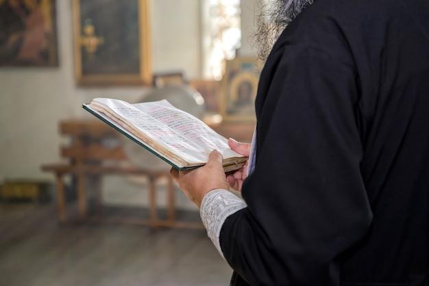O livro com orações nas mãos de um padre ortodoxo